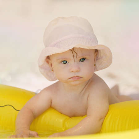 downs syndrome: cheerful little baby girl with Downs Syndrome playing in the pool