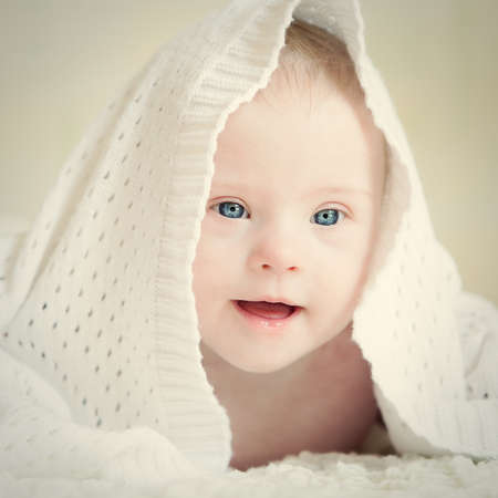 eyes looking down: Little baby with Down syndrome hid under blanket Stock Photo