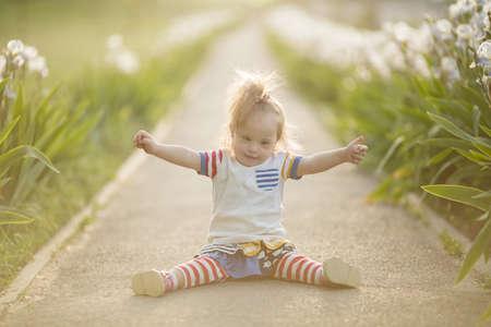 Divertida niña con síndrome de Down se arrastra a lo largo del camino Foto de archivo - 30852200