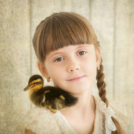 portrait of girl with duckling on shoulder