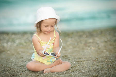 Little girl with Down syndrome playing sunglasses on the beach