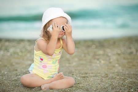 little girl wears glasses at the beach photo