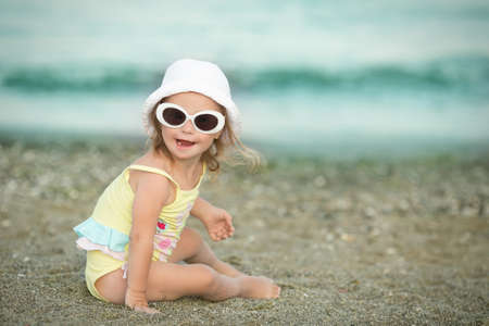 little girl wears glasses at the beach