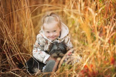 Hermosa chica con síndrome de Down abrazos cachorro Foto de archivo - 36622974