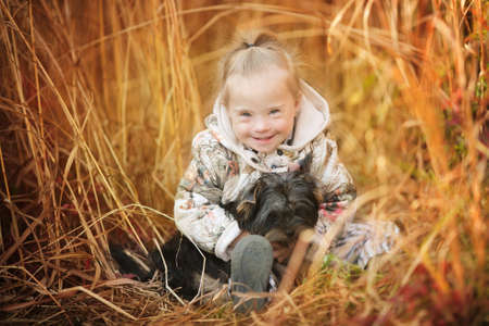beautiful girl with Down syndrome hugs puppy
