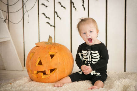 Hermosa niña con síndrome de Down se sienta cerca de una calabaza en Halloween vestido como un esqueleto Foto de archivo - 36622983
