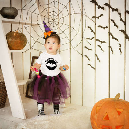 Little girl in costume Halloween witch on a holiday photo