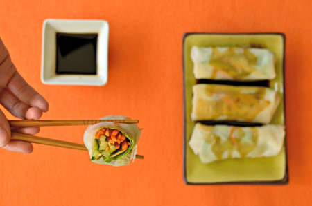 Summer rolls filled with raw vegetables with a container of soy sauce. Closeup on an opened summer roll held with chopsticks