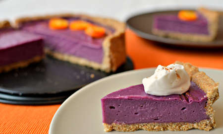 Spicy purple yam pie with coconut whip. This pie is vegan, gluten-free and sugar-free. Slice on a white plate. Orange background Stock Photo