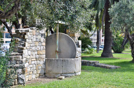 millstone crusher in a garden with olive trees