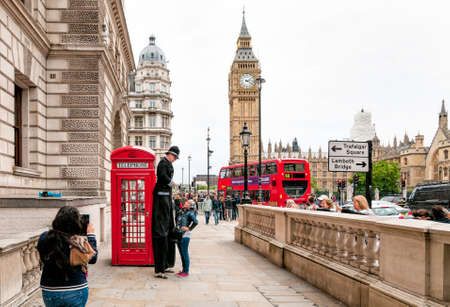 LONDON, ENGLAND - SEPTEMBER 15, 2013: Street artist perform in front of a red phone booth with the Big Ben in background