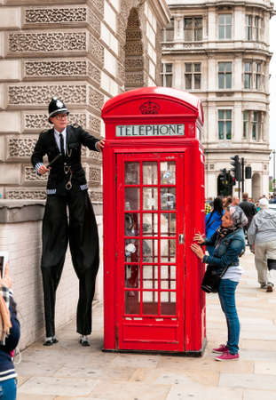 LONDON, ENGLAND - SEPTEMBER 15, 2013: Street artist perform in front of a red phone booth