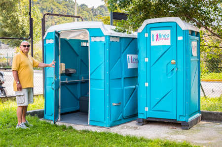 latrine: Blue portable toilet cabins in the park with a man of entrance.