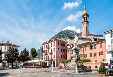 LECCO, ITALY - AUGUST 28, 2015: Central square XX Settembre of the center of Lecco with Monument to Mario Cermenati and bell tower of the basilica. 新聞圖片