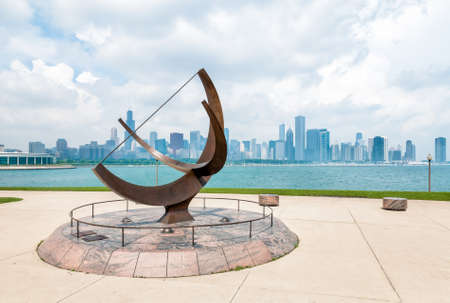 lakefront: Bronze sculpture located on the Lake Michigan lakefront outside the Adler Planetarium, as seen Chicago skyline blur in the background. Main focus on scultur.