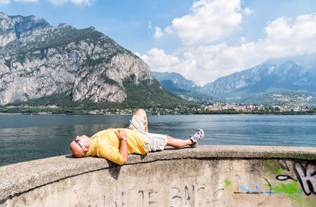 man lying down: Bald man lying down on the shore of lake Como, in front of the town Lecco in Italy, with mountain in background. Stock Photo