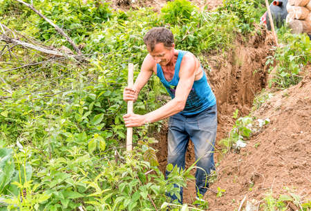 Man digging the ground with a spade