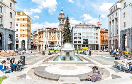 VARESE, ITALY - MAY 6, 2016: Monte Grappa square, located in the historic center. A tall fir tree and the streaming fountain dominated the square. It was built in 1927 under fascist regime, Varese When Became provincial capital.