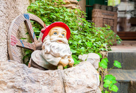 gnome: Garden gnome with a red hat near the green bush looking up