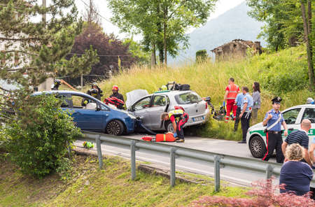 tending: Ferrera di Varese, Varese, Italy - June 16, 2016: Road accident and rescue workers tending to car accident victim.