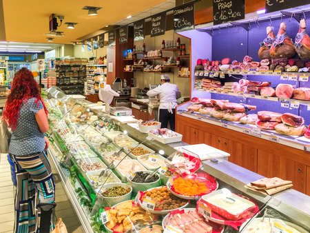 jamones: Varese, Italy - June 9, 2016: Shopping hams, cheeses and other gastronomy in the supermarket.