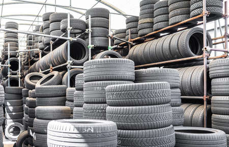 Stack of used tires in a car garage of installation service. Standard-Bild