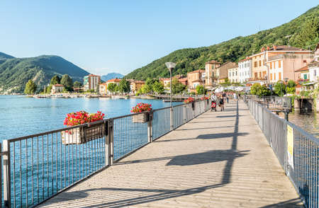 Porto Ceresio, Varese, Italy - July 3, 2016: People are walking along the lakeside of Porto Ceresio, is delicious Italian town on Lake Lugano.
