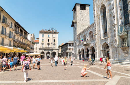 Como, Lombardy, Italy - July 19, 2016: People visiting the Piazza Duomo with bars and restaurants in the historic center of Como.