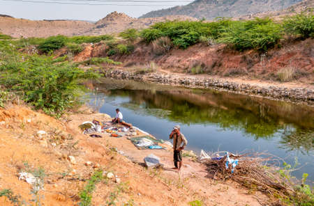 Puttaparthi, Andhra Pradesh, India - January 11, 2013: A Man washing clothes on the banks of the river at the village of Puttaparthi. Editorial