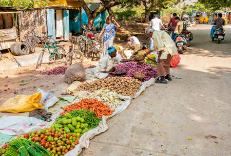 retailers: Puttaparthi, Andhra Pradesh, India - January 13, 2013: Indian man sell vegetables at street market of Puttaparthi. Editorial