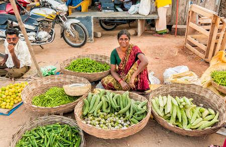 Puttaparthi, Andhra Pradesh, India - January 13, 2013: Indian woman sell vegetables at street market of Puttaparthi.