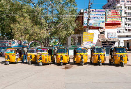 Puttaparthi, Andhra Pradesh, India - January 13, 2013: Yellow rickshaw taxis on a road in Puttaparthi village. Editorial