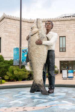 public aquarium: Chicago, Illinois, USA - August 25, 2014: The Man With Fish Statue is located outside the Chicago Shedd Aquarium