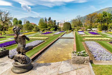 Landscape of the Botanical Garden of Villa Taranto with bronze statue The Fisher in front, Pallanza, Verbania, Italy.