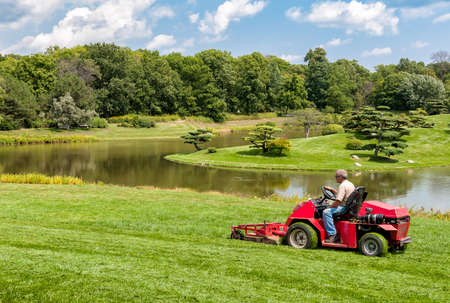 Chicago, IL, United States - August 18, 2014: Worker with tractor mower in the Chicago Botanic Garden. Editorial
