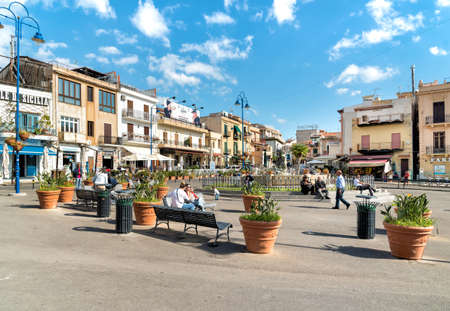 People resting on the square in the center of Mondello, is a small seaside resort near Palermo city center.