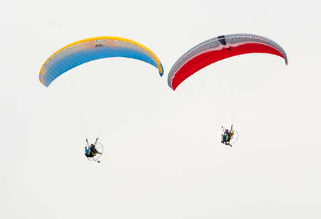 Paragliders flying in the sky on a paramotors demonstration of air show. Editorial