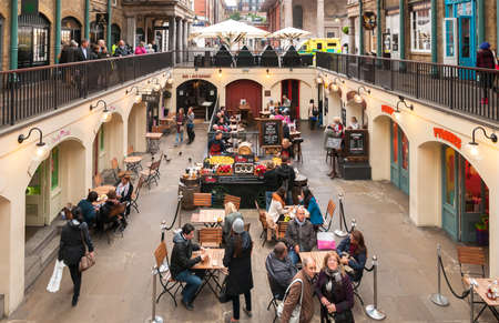 People enjoying Paella in the Covent Garden Apple Market, is the big attraction for its restaurants, pubs, market stalls and shop in London. Editorial