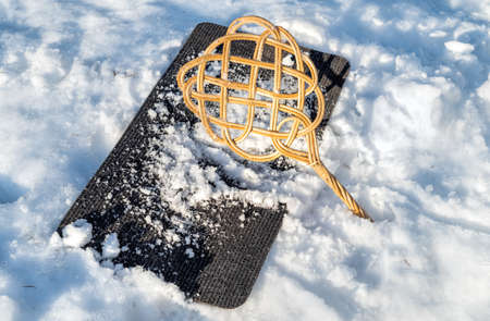 Carpet beater on carpet with snow for winter cleaning.
