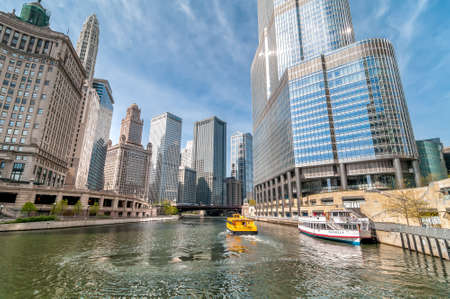 Chicago, Illinois, USA - April 13, 2012: View of Chicago skyscrapers with Watertaxi and Wendell sightseeing boat cruising on the Chicago river between the Donald Tramp Tower and the Mather Tower in Chicago. Editorial