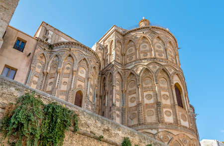 The outsides of the main doorways and their pointed arches of the ancient Cathedral Church in Monreale, Sicily, Italy