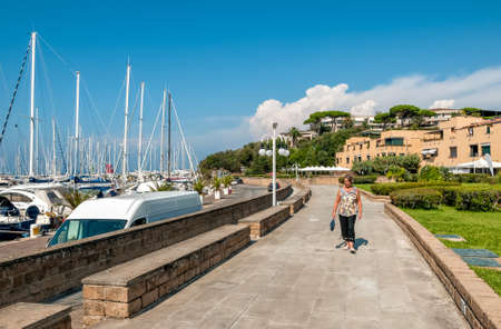 View of center of Punta Ala with Elderly woman walking alone on the promenade near of the harbor, province of Grosseto in Tuscany, Italy