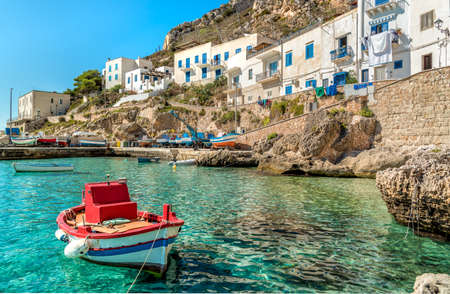 View of Levanzo Island with fishermans boat in the foreground, the smallest of the three Aegadian islands in the Mediterranean sea of ??Sicily, Trapani, Italy