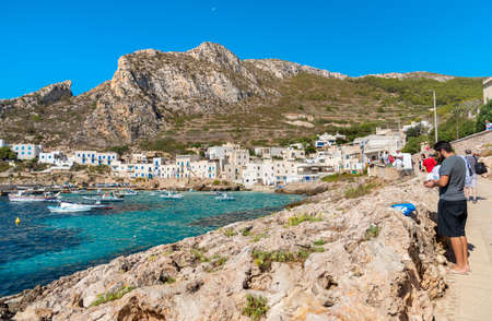 Levanzo, Sicily, Italy - September 22, 2016: Visitors enjoy the coastline on their trip to the small village on Levanzo island, the smallest of the three Aegadian islands in the Mediterranean sea.