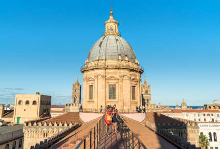 Palermo, Sicily, Italy - October 5, 2017: People walking on the roof of the Palermo Cathedral in the evening against sunlight.