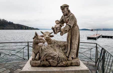 Statues of Saint Francis with Jesus child on Lake Maggiore in Laveno Mombello, Italy 報道画像
