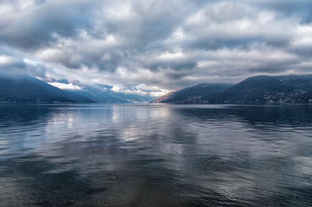 Landscape of Lake Maggiore with cloudy sky and Swiss mountains in the background, Luino, Italy