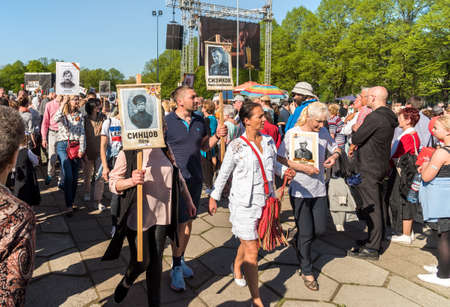 Riga, Latvia - May 9, 2018: Procession of people with flags and their relatives in Immortal Regiment on annual Victory Day in the Victory park of Riga, Latvia
