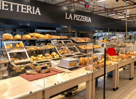 Varese, Italy - Marc 7, 2019: Bakery department with fresh bread on shelves inside of the IPER of Varese, hypermarket, interior of the shopping center, Varese, Italy