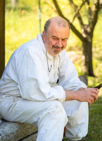 Angry Senior man in white dress resting in the garden.